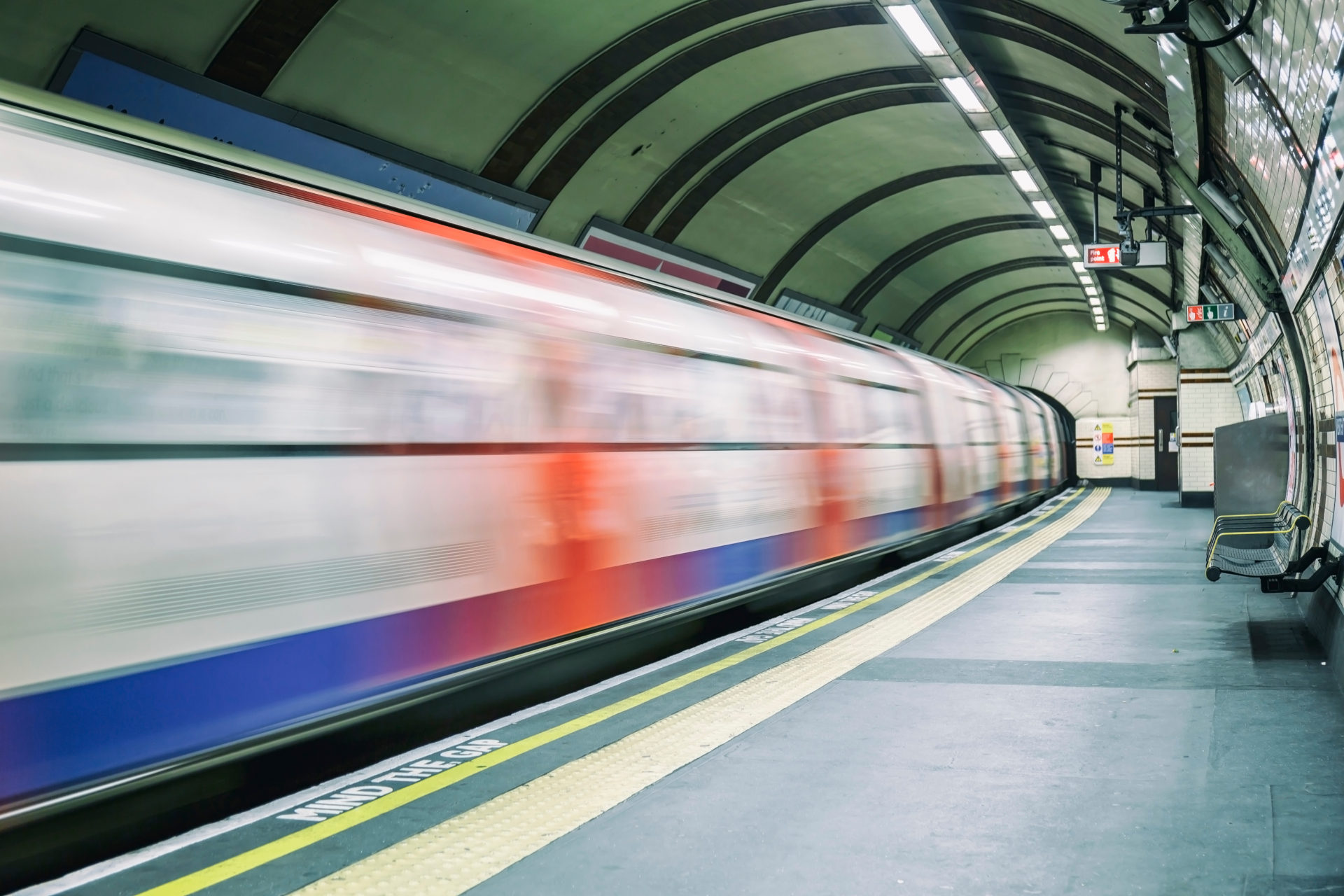 Tube leaving the platform at an underground station in London.